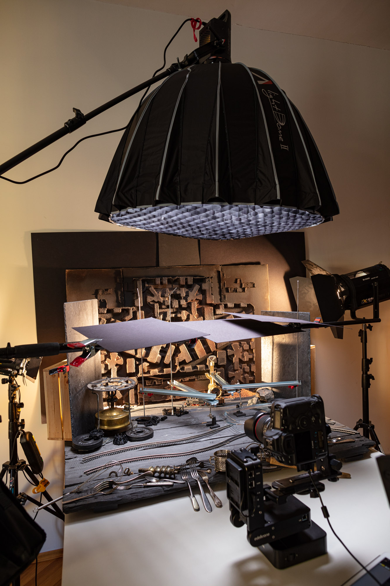 """Behind the scenes at the video production of """"Vegan Cherry Crumble Pie Recipe"""". A big table set up resembling a """"pie factory"""". In a studio with various lamps and cameras."""