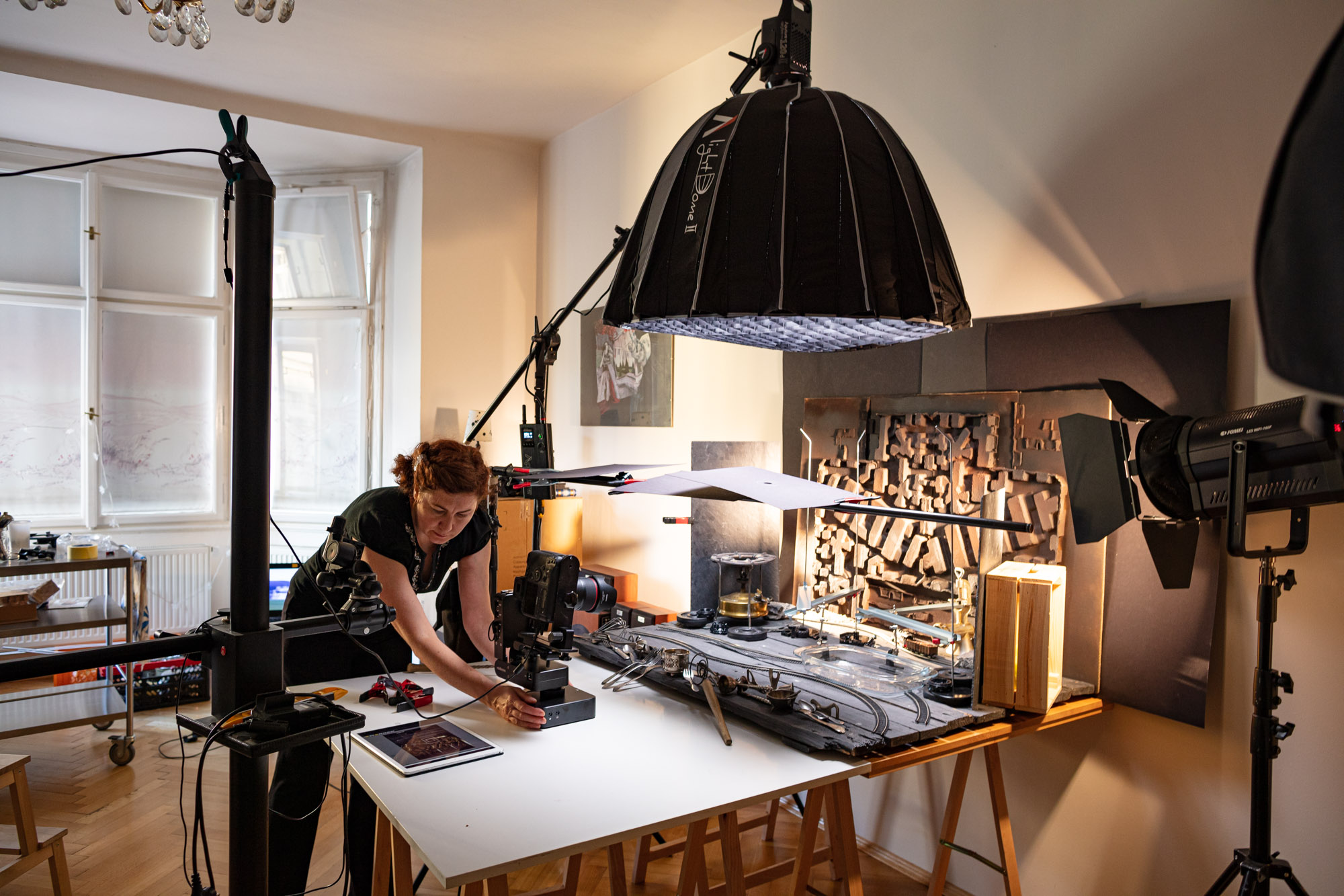 """Behind the scenes at the video production of """"Vegan Cherry Crumble Pie Recipe"""". A big table set up resembling a """"pie factory"""". In a studio with various lamps and cameras. The stylist/art director is checking the angle and camera movement."""