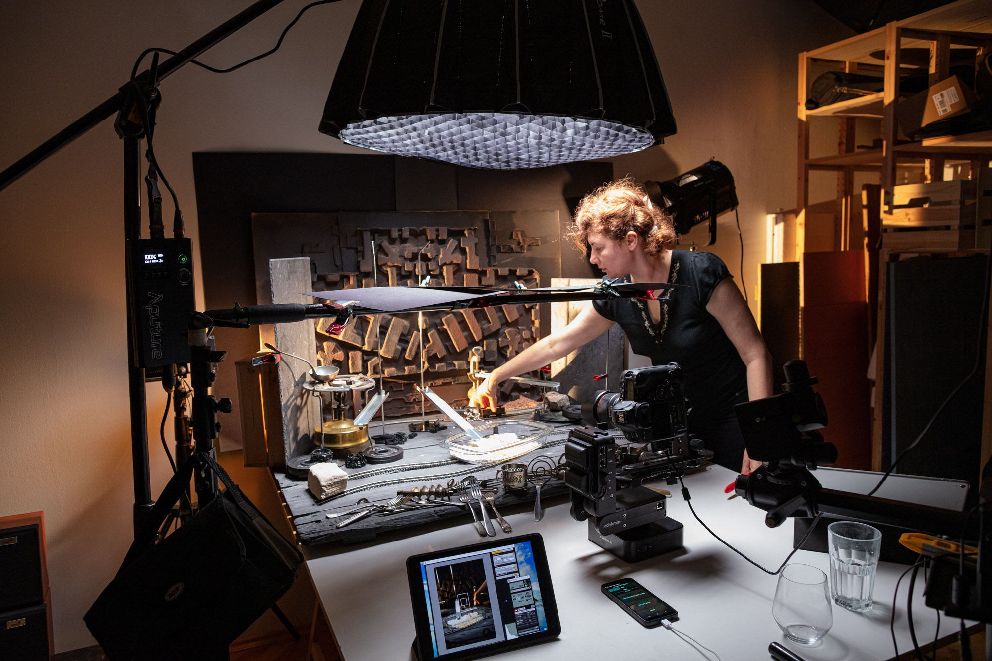 """Behind the scenes at the video production of """"Vegan Cherry Crumble Pie Recipe"""". A big table set up resembling a """"pie factory"""". In a studio with various lamps and cameras. The stylist/art director is preparing the scene."""