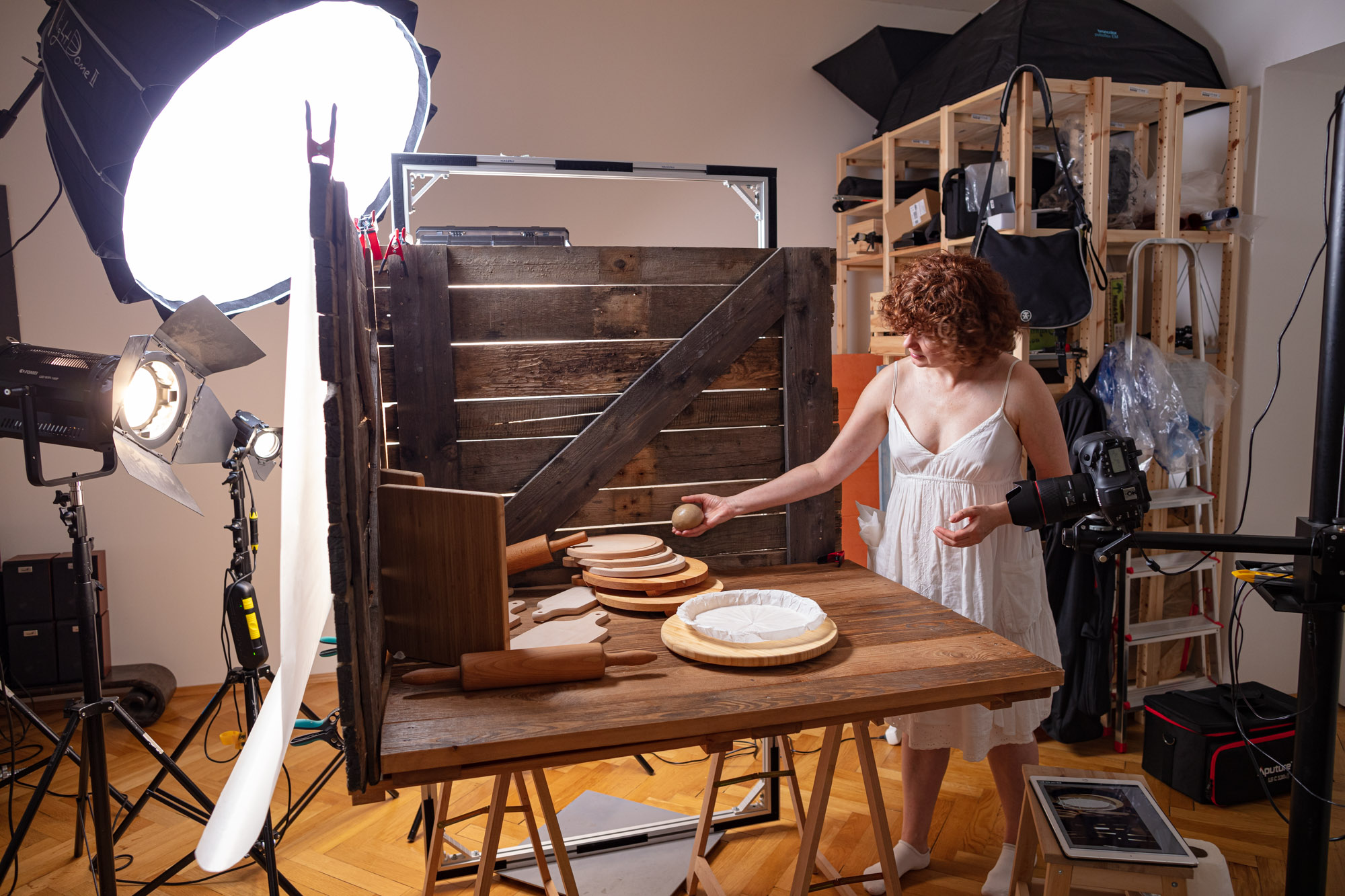 """Behind the scenes at the video production of """"Vegan Cherry Crumble Pie Recipe"""". A big table set up resembling a """"barn"""". In a studio with various lamps and cameras. The stylist/art director is preparing the scene."""