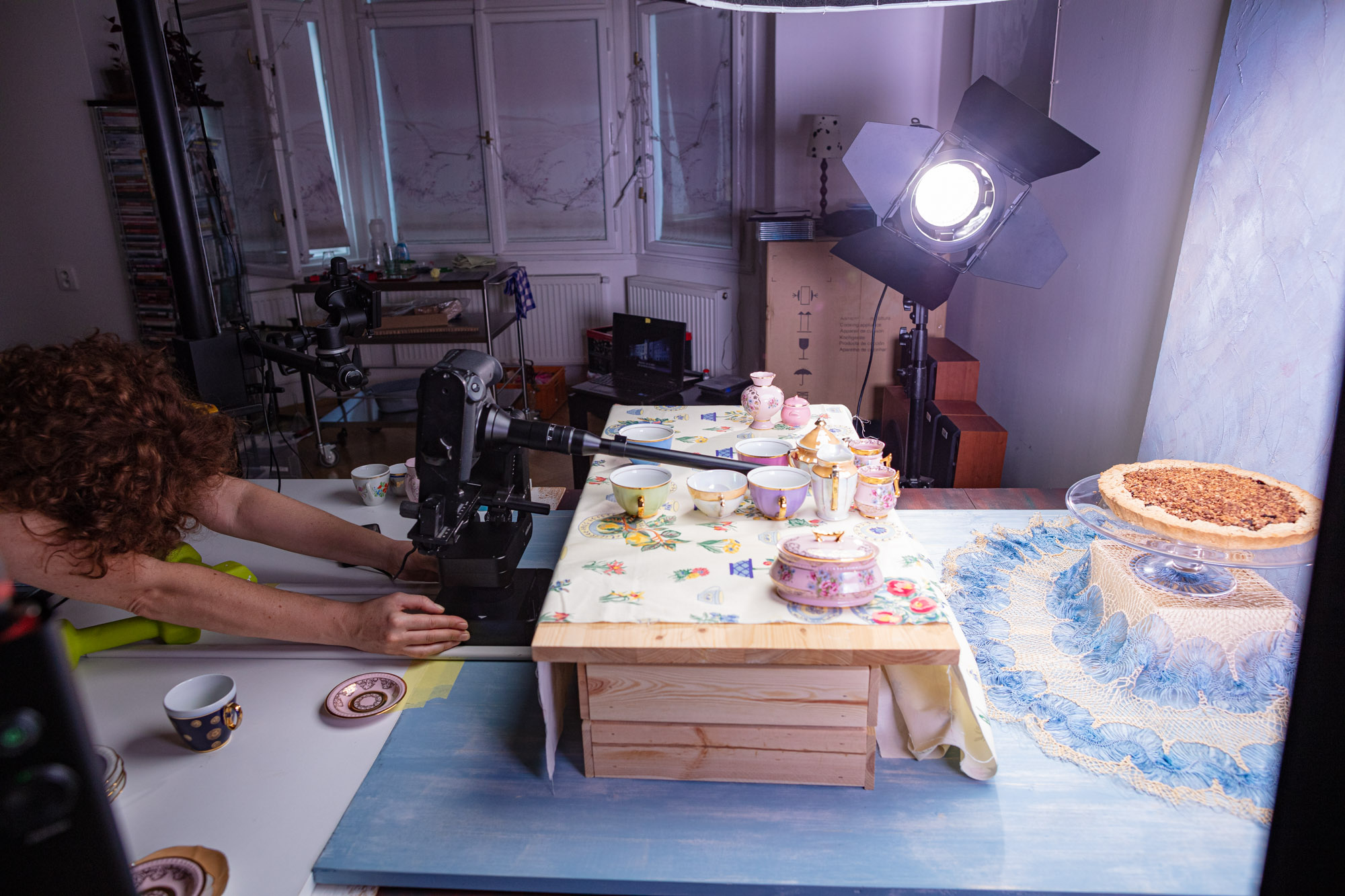 """Behind the scenes at the video production of """"Vegan Cherry Crumble Pie Recipe"""". A big table set up resembling a """"decorated table"""". In a studio with various lamps and cameras. The stylist/art director is checking the angle and camera movement."""