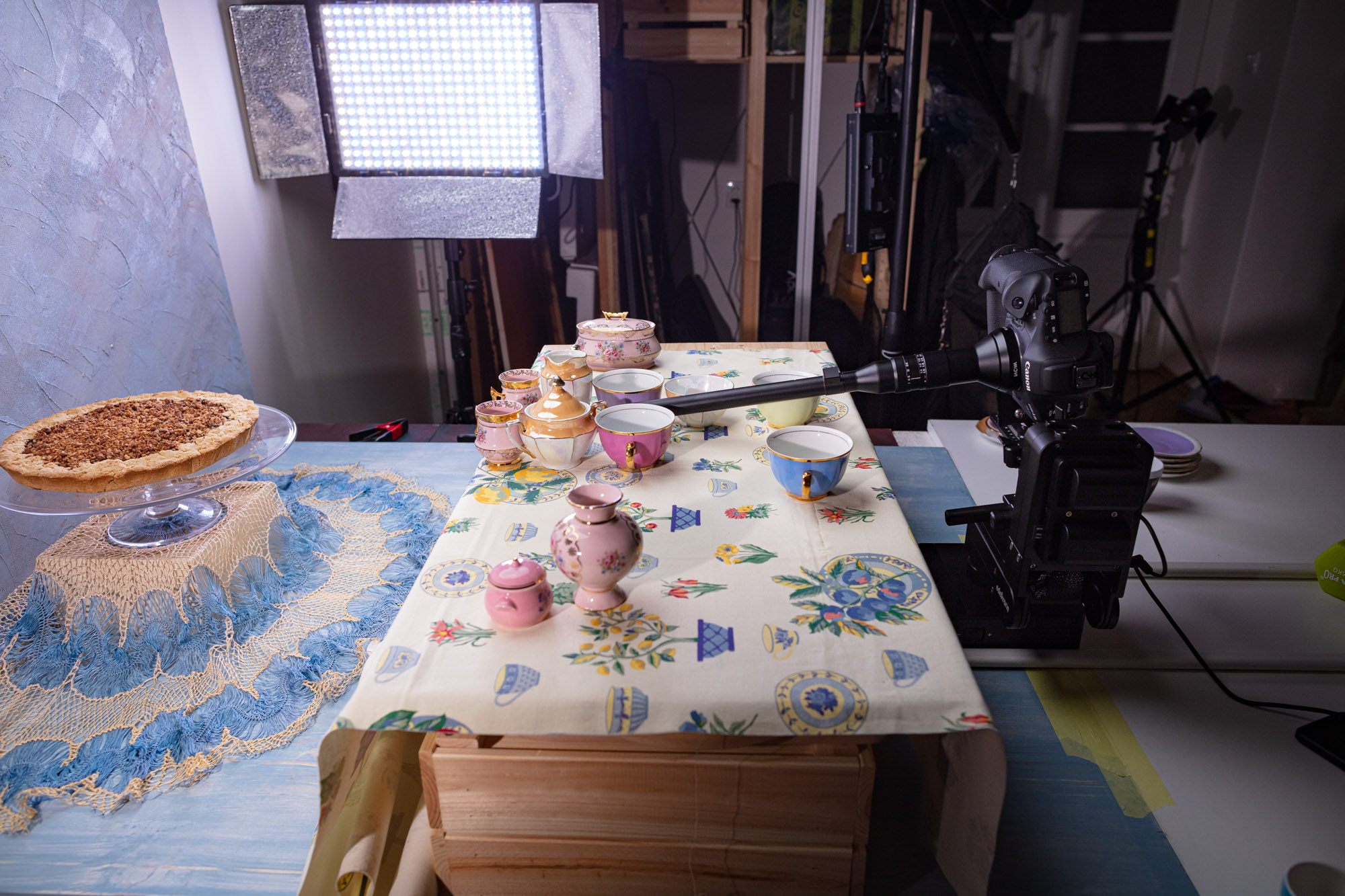 """Behind the scenes at the video production of """"Vegan Cherry Crumble Pie Recipe"""". A big table set up resembling a """"decorated table"""". In a studio with various lamps and cameras."""