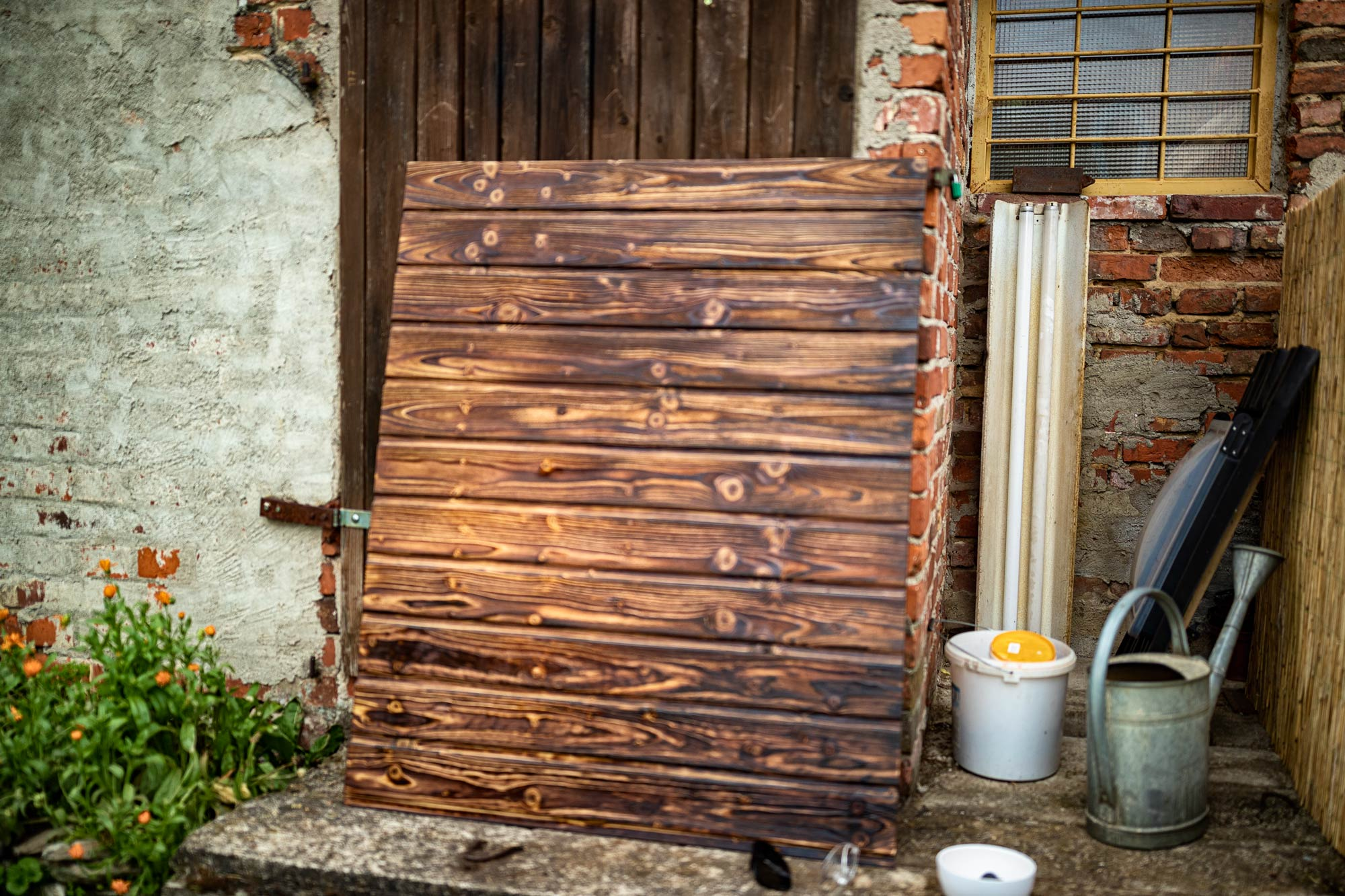Building photographic backgrounds. A Painted wooden desks leaned against a wall in a garden.