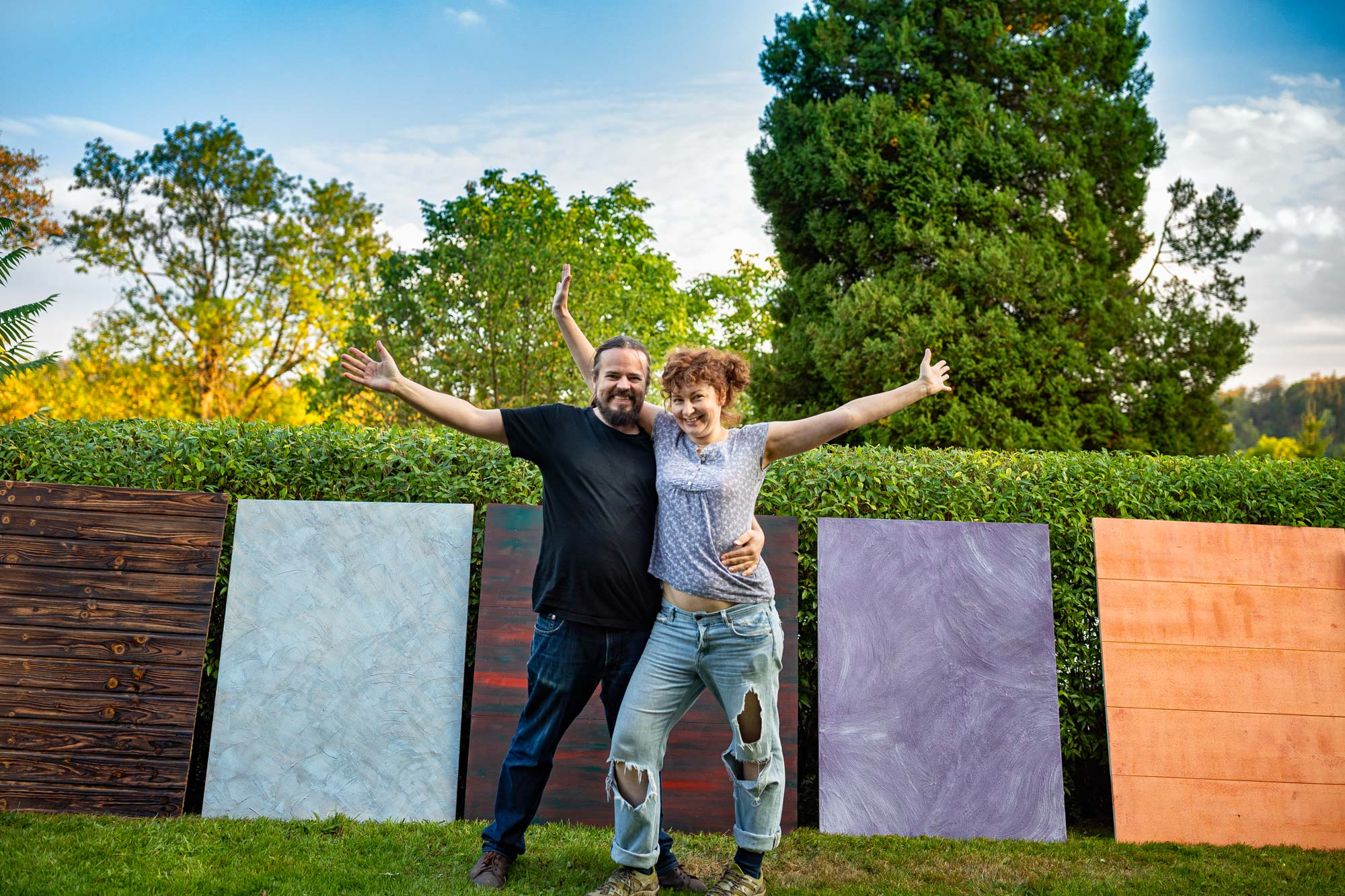 Me and Ellen standing in front of some finished painted photographic backgrounds leaned against a garden hedge.