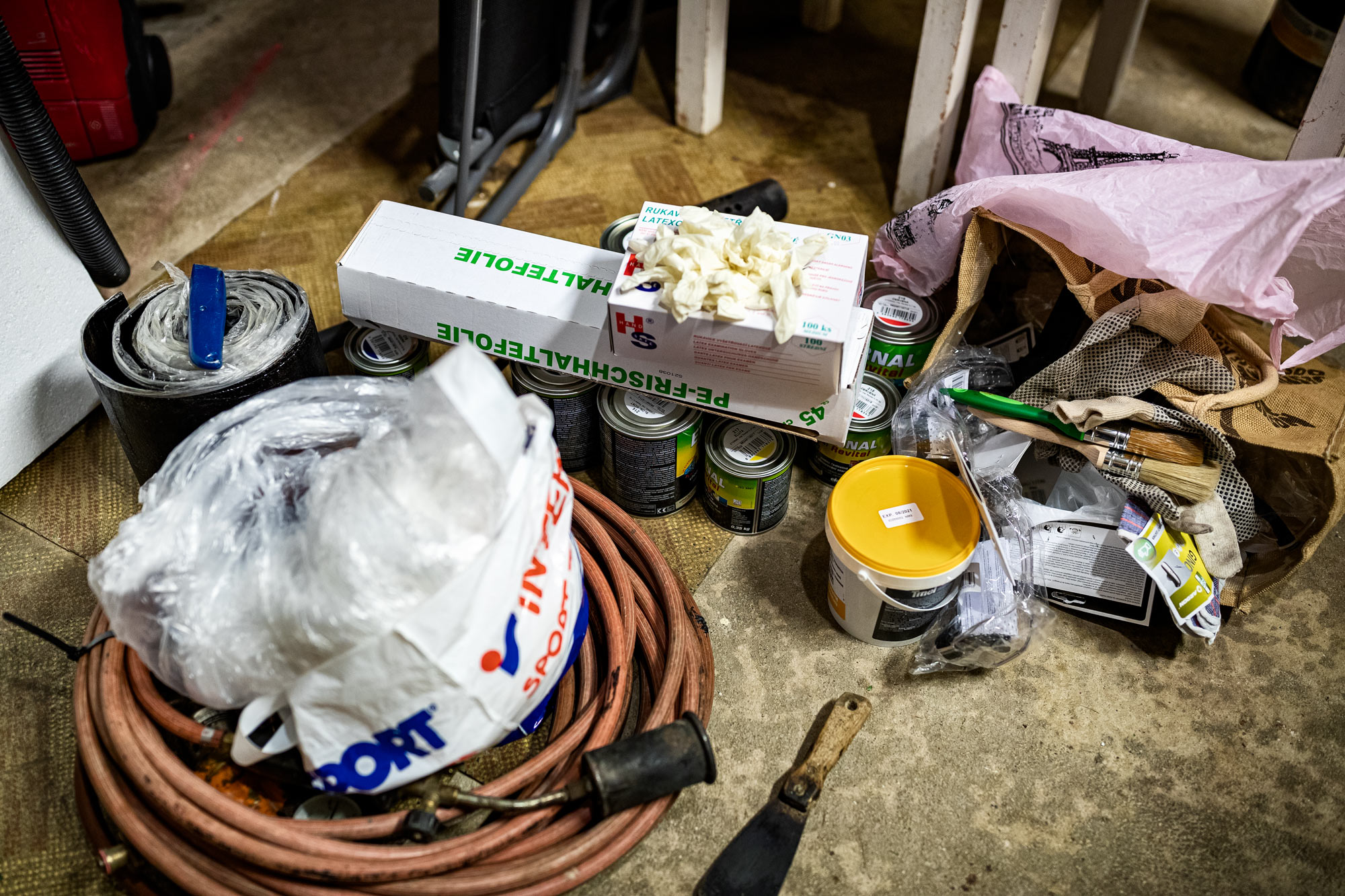Buckets of paint, a blow torch, brushes and other tools and utensils laying on the floor.