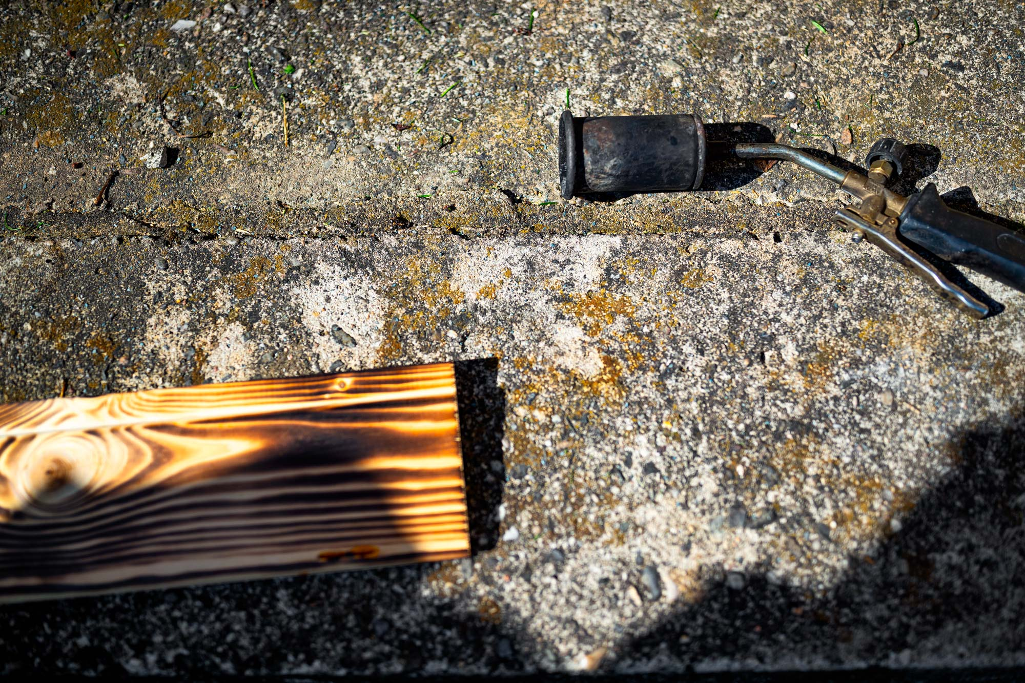 Building photographic backgrounds. A blow torch burning next to a wooden desk.