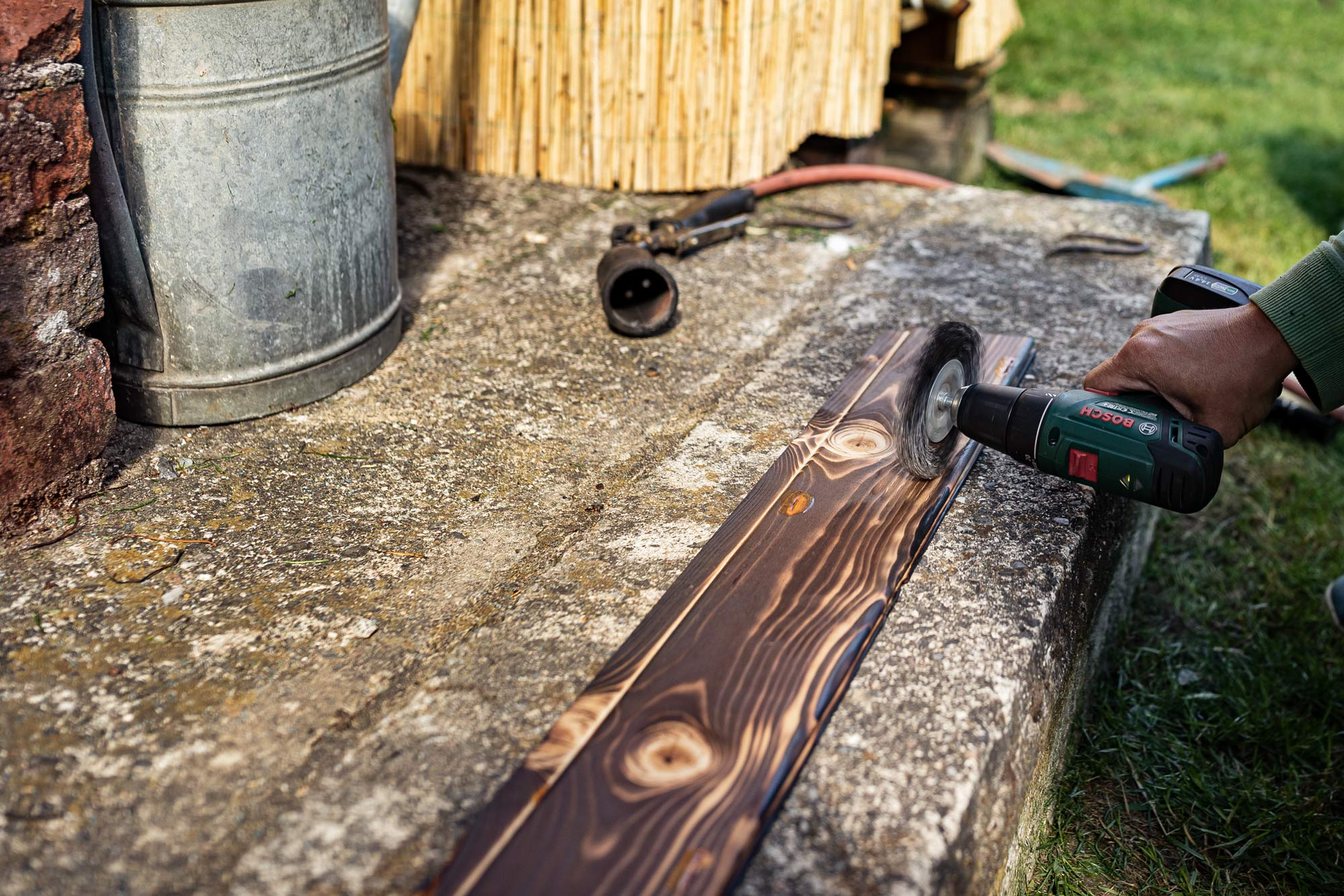Building photographic backgrounds. A hand holding an electric emery sanding a piece of wood.