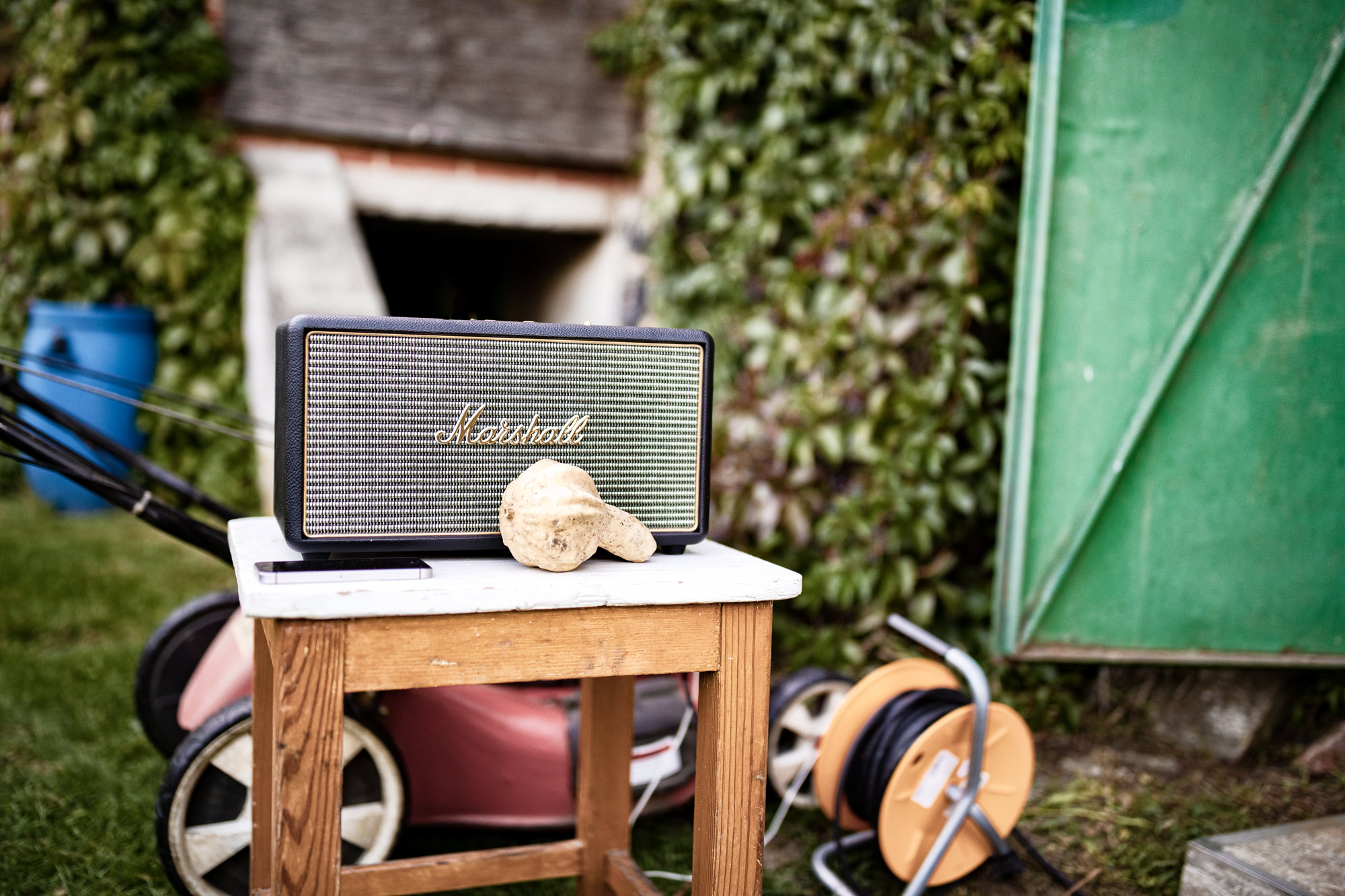 Building photographic backgrounds. A speaker/radio on a table in the garden with a mower blurred in the background.