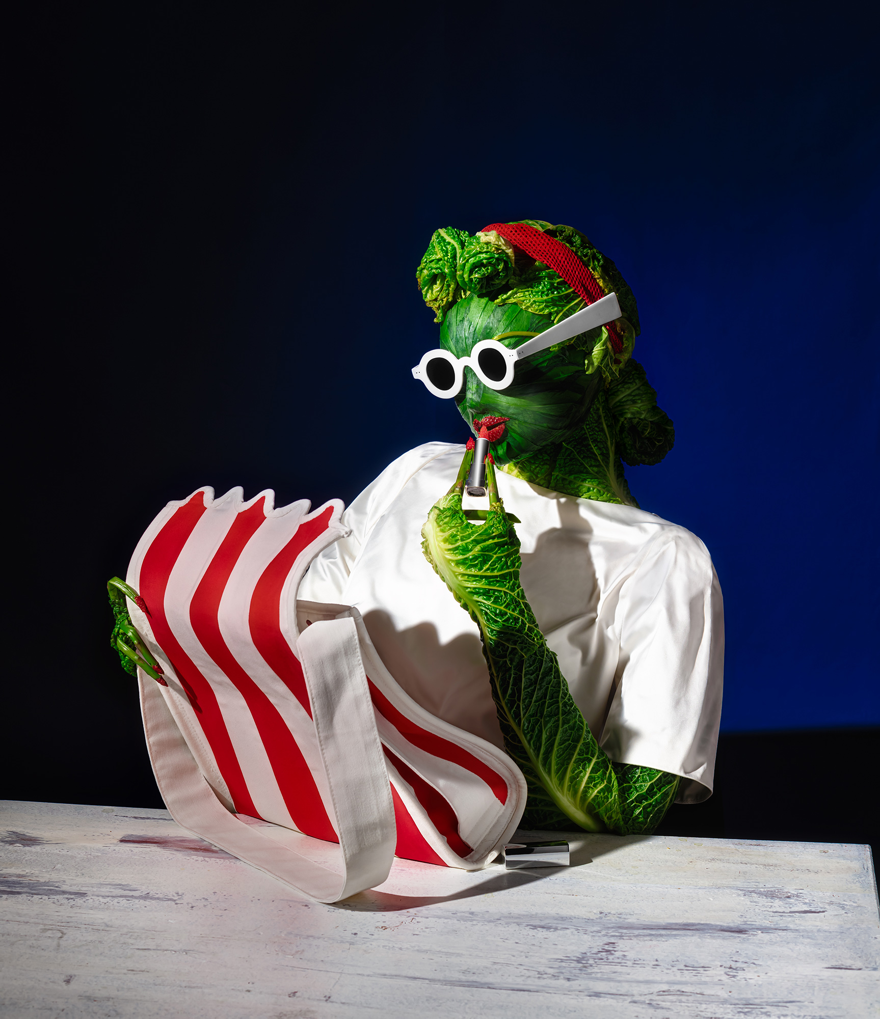 Fashion meets food, veggie sculpture doing her make up with white and red striped handbag.