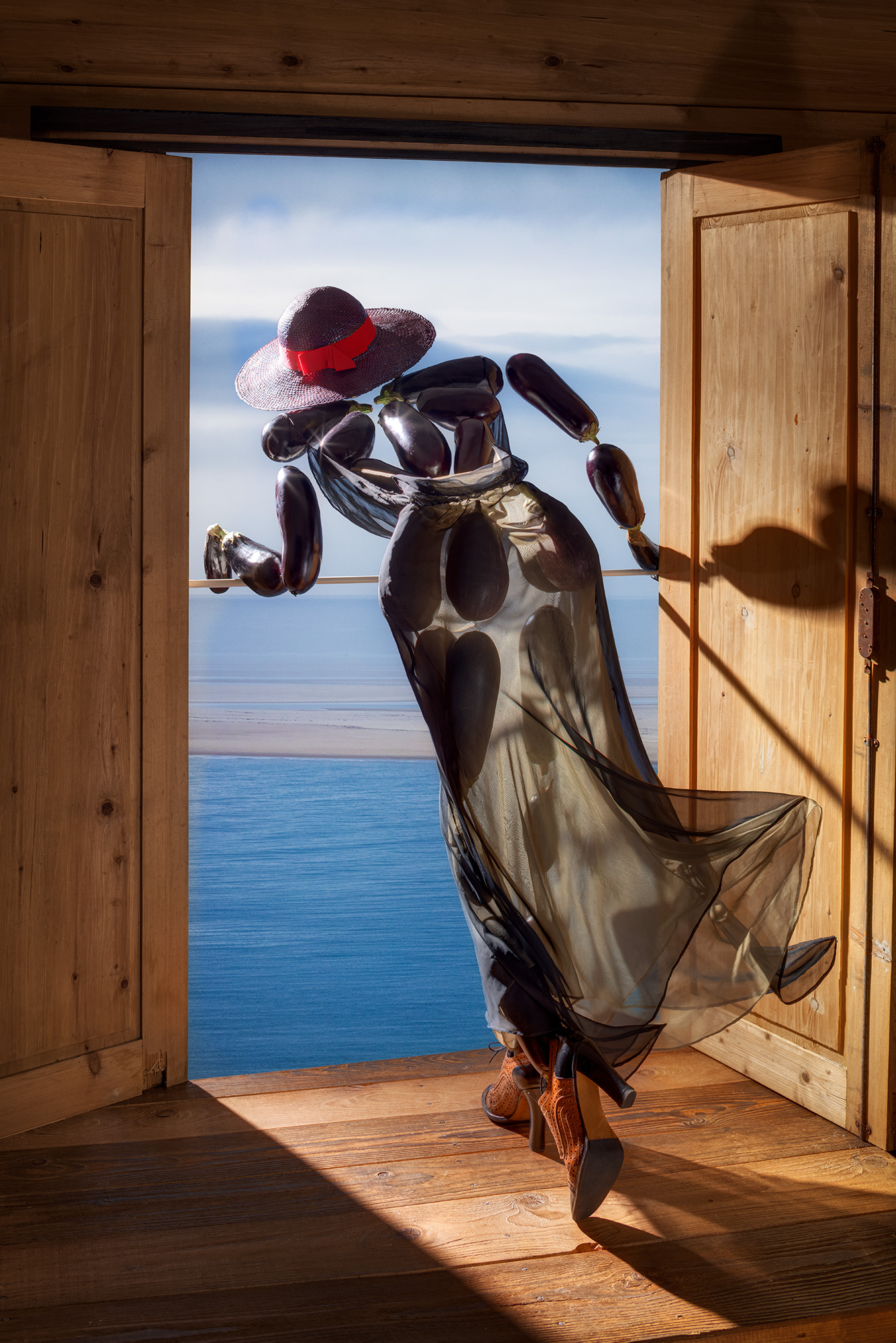 Fashion meets Food. eggplants, aubergines put together the figure of a women leaning elegantly out a door overlooking the ocean. Hat with summer dress.
