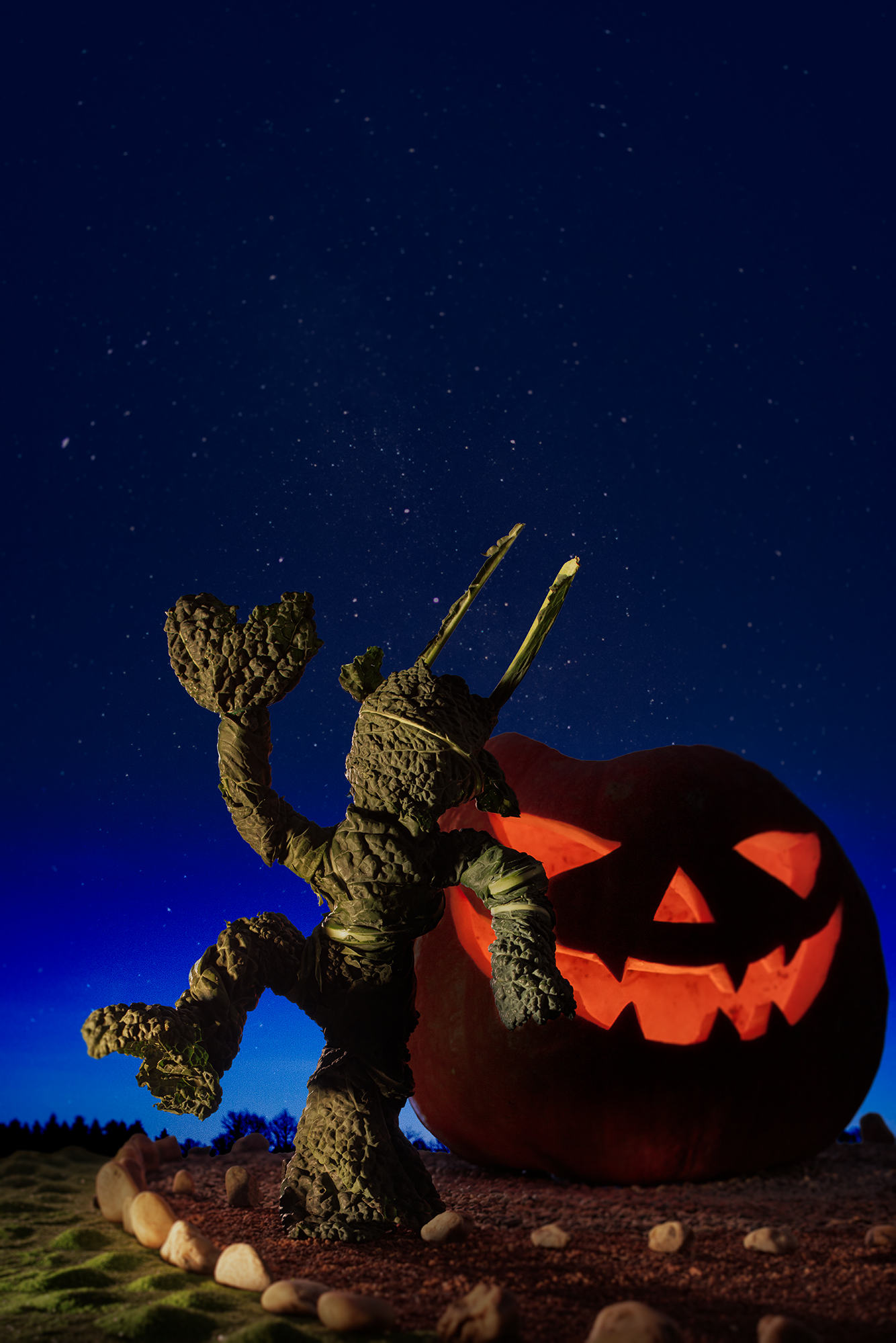 A figure made out of kale is shown in front of a lit pumpkin with carved out face.