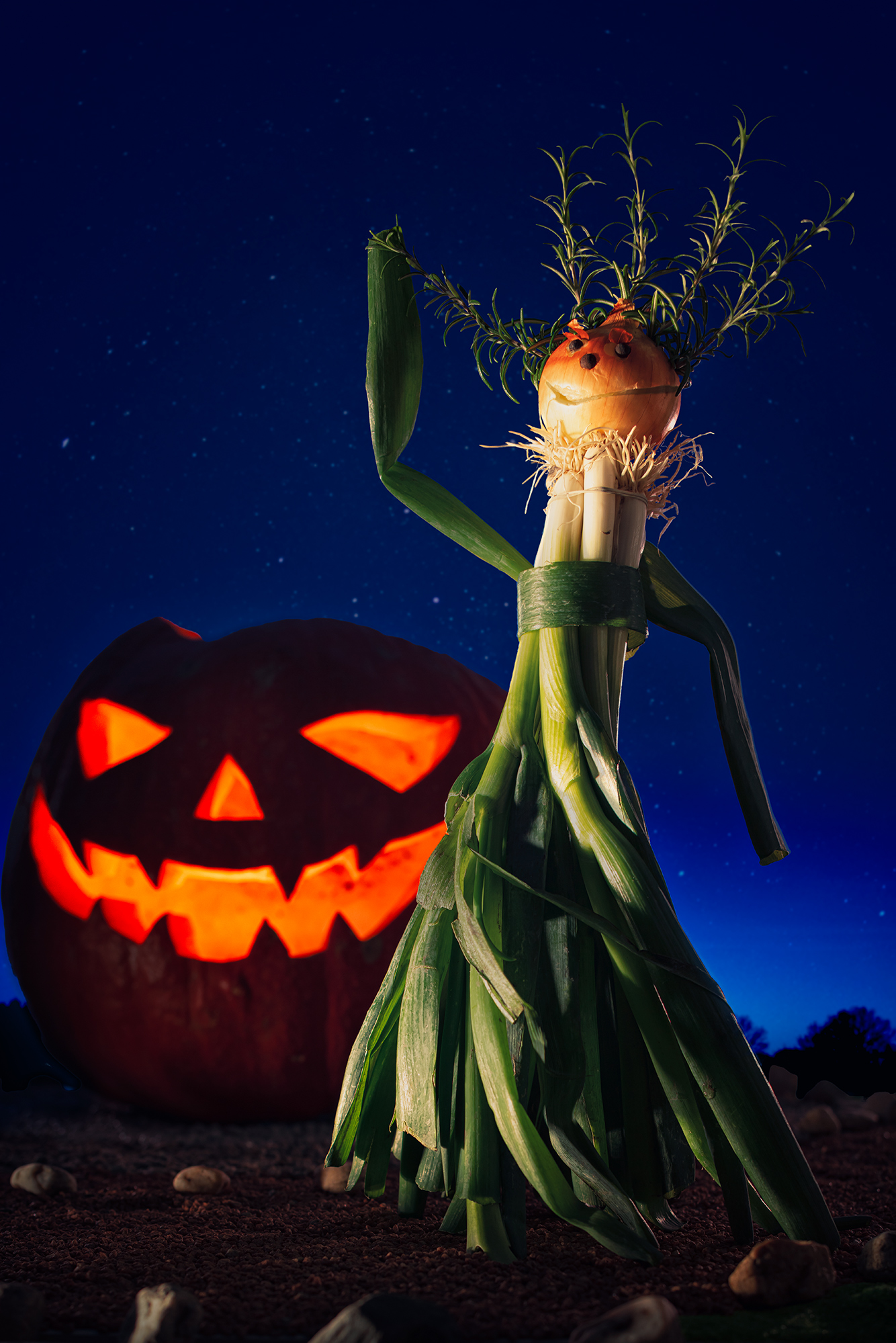 A figure made out of spring onion and yellow onion is shown in front of a lit pumpkin with carved out face.