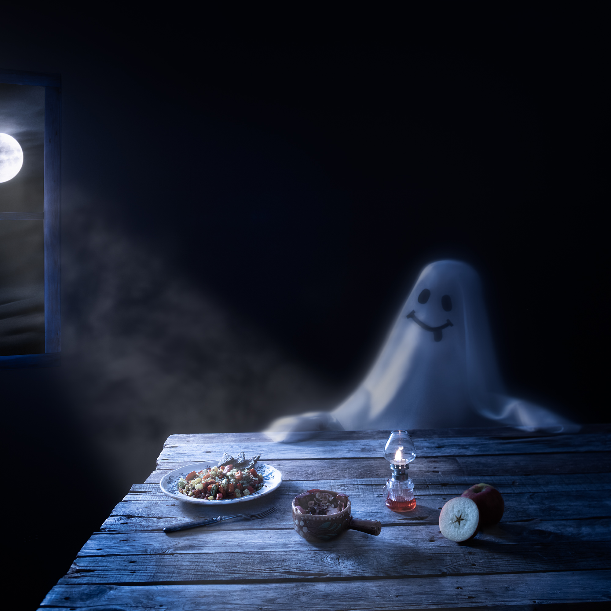 A smiling ghost is seen sitting by a table. A plate filled with autumn salad with cavolo nero is set and the moon is shining through a window.