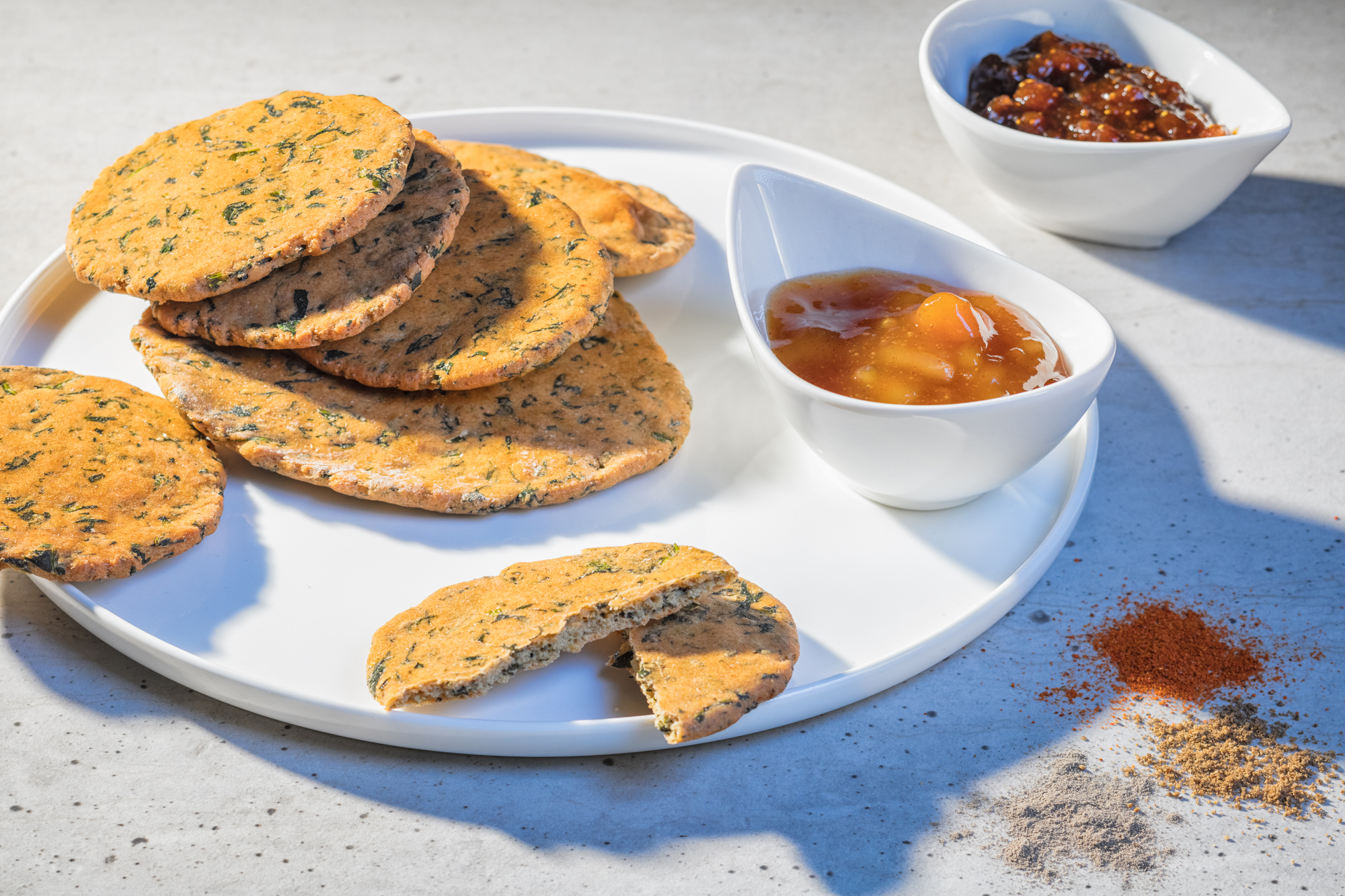 A white plate with Spinach-lentil Cookies, a dish with grape chutney and another dish with a spicy Indian sauce. depicted in bright afternoon summer light on a grey table. Three little hives of different spices are next to the plate.
