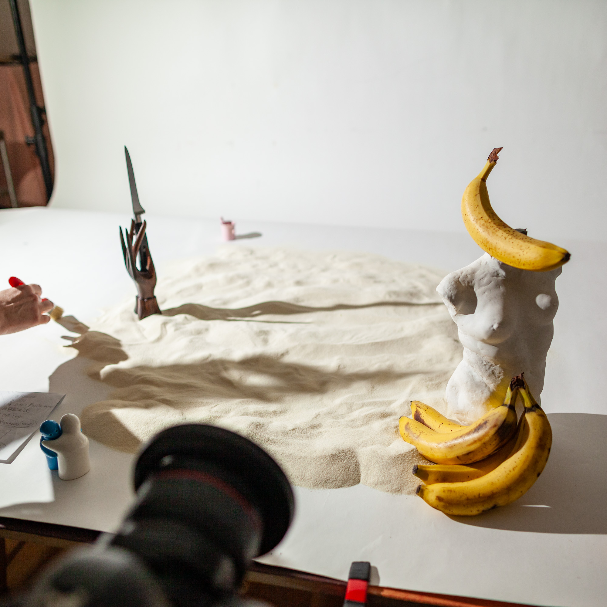 Behind the scenes of vegan banana bread recipe. The photo shows the preparation of a scene. A statue of a naked women's torso decorated with bananas is seen as well as a wooden hand holding a knife.