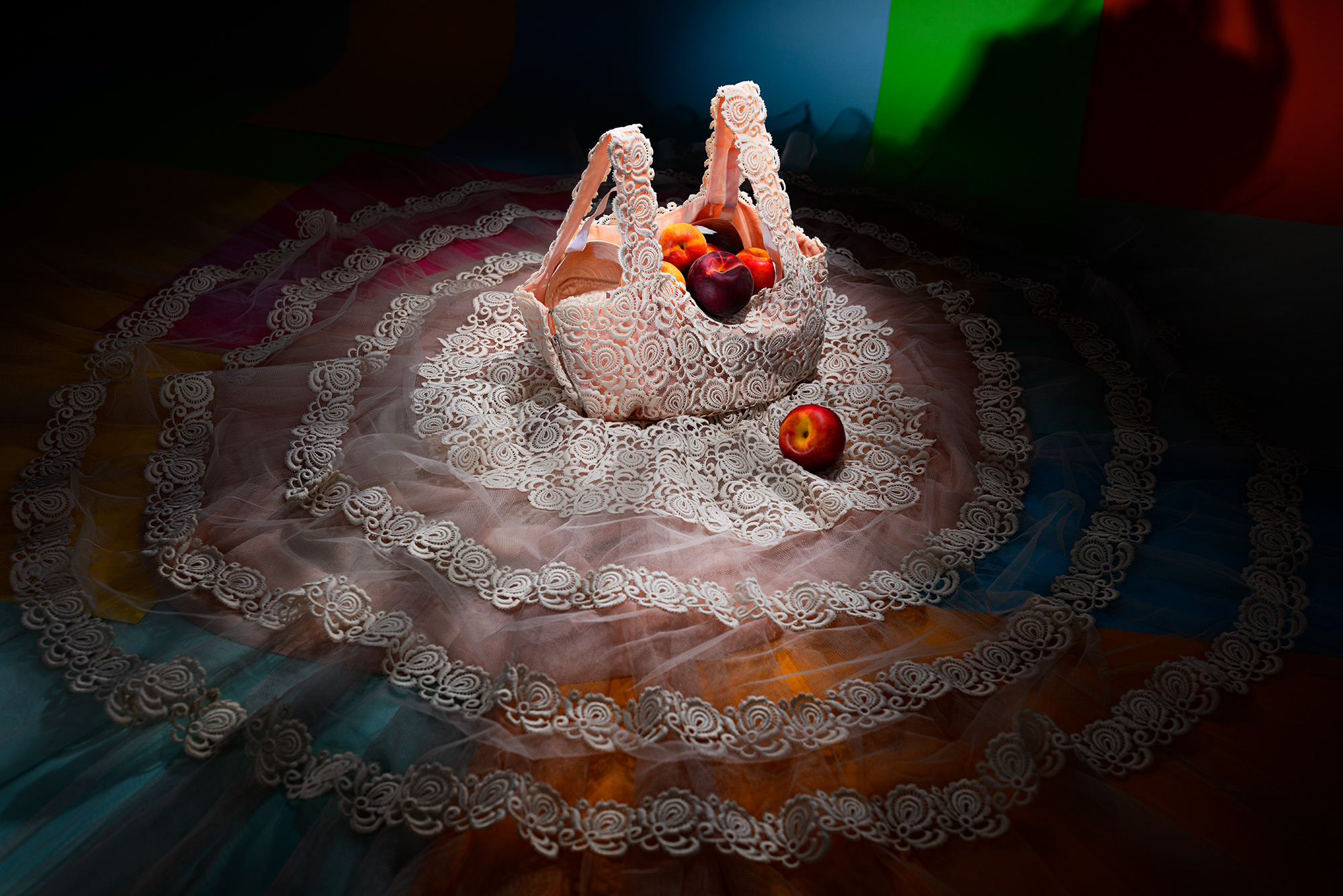 Fashion meets food. A laced dress from the 1950's is laied out on the floor and filled with peaches.