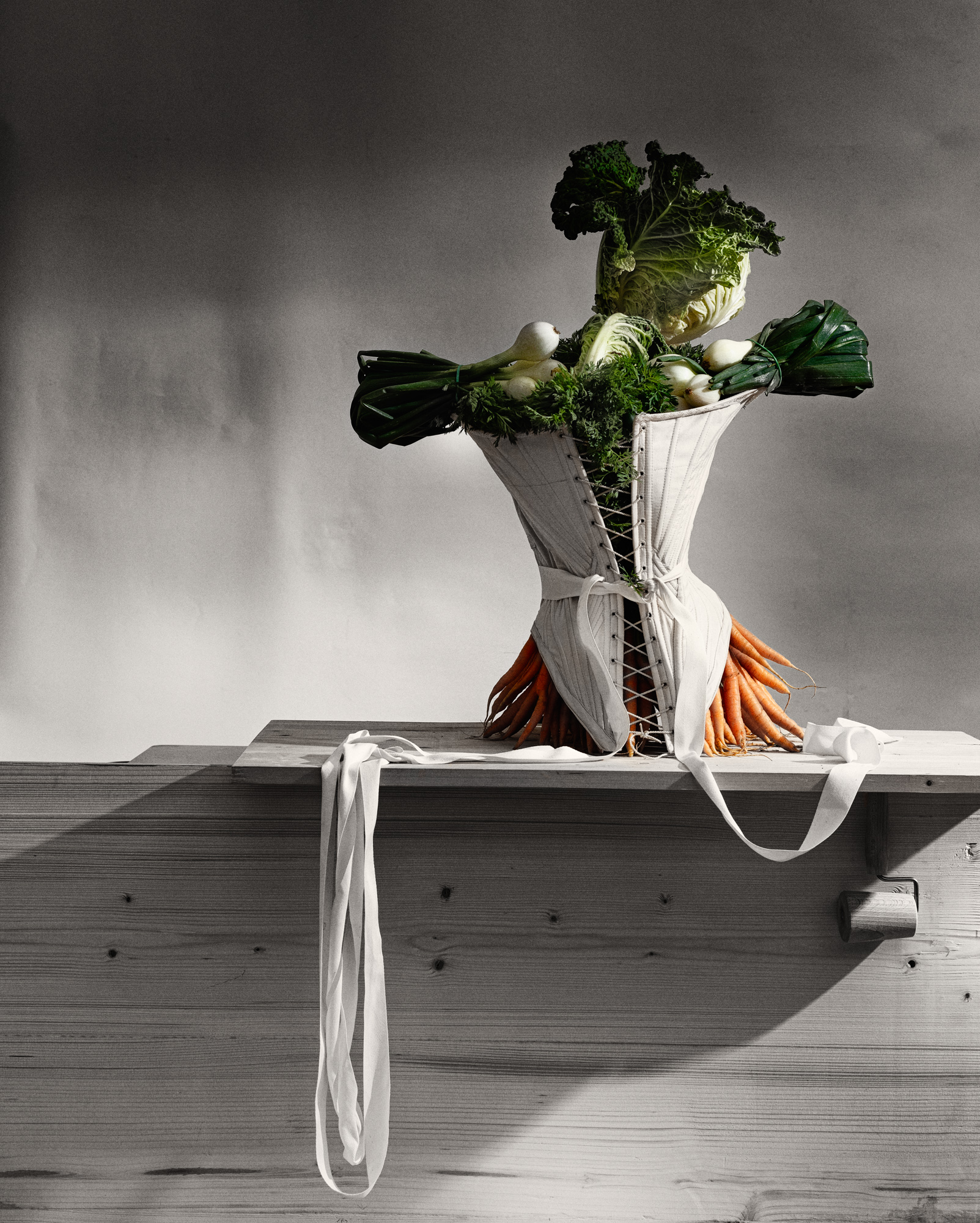 When fashion meets food. A cabbage, carrots and onions put together into a corset, resembling the figure of a woman leaning elegantly on a bench with the back to the viewer.
