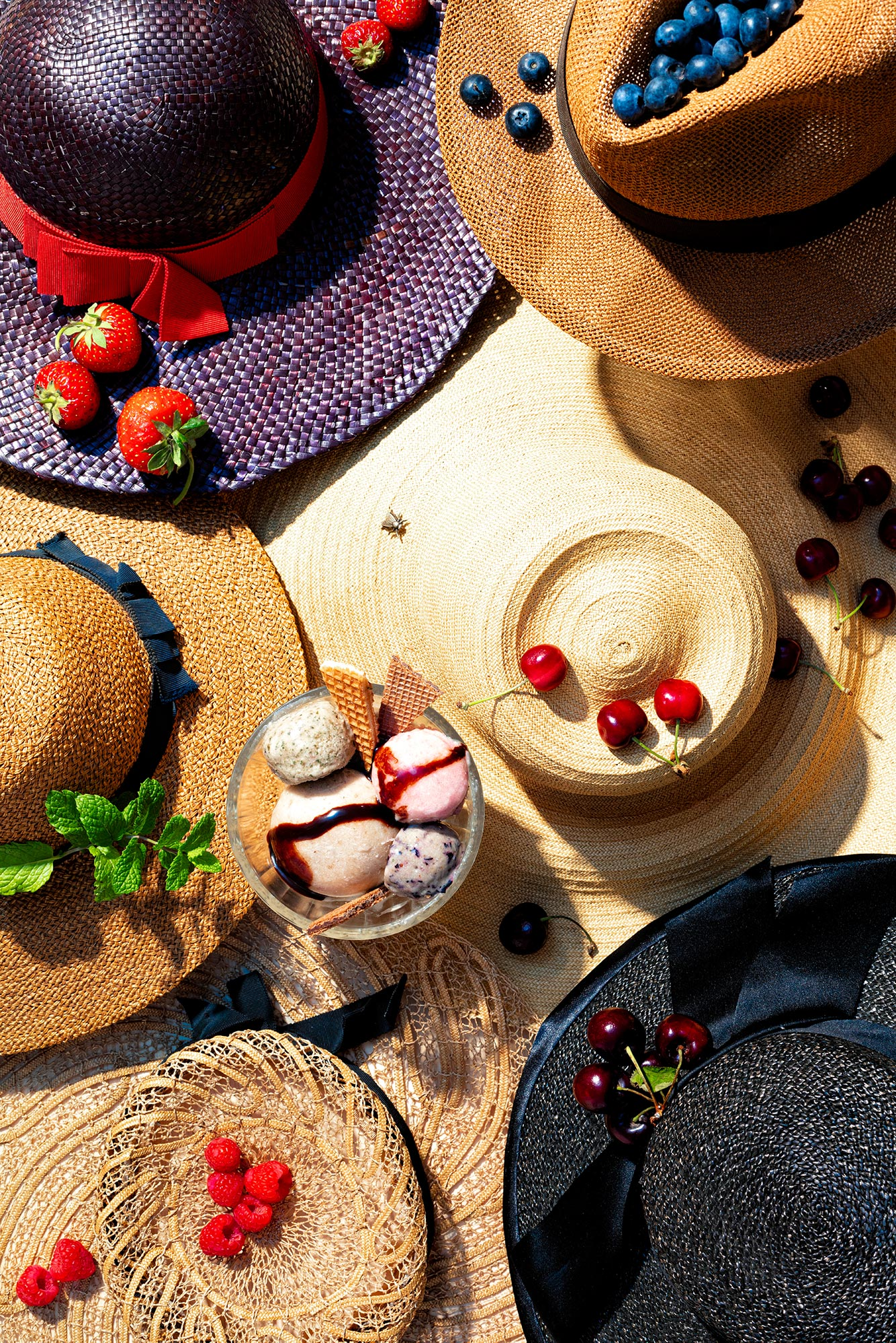 Fashion meets Food. Six summer hats in different colors and shapes are put together, lit in afternoon summer light. On them there are strawberries, blueberries, cherries and raspberries as well as a dish of ice cream arranged.