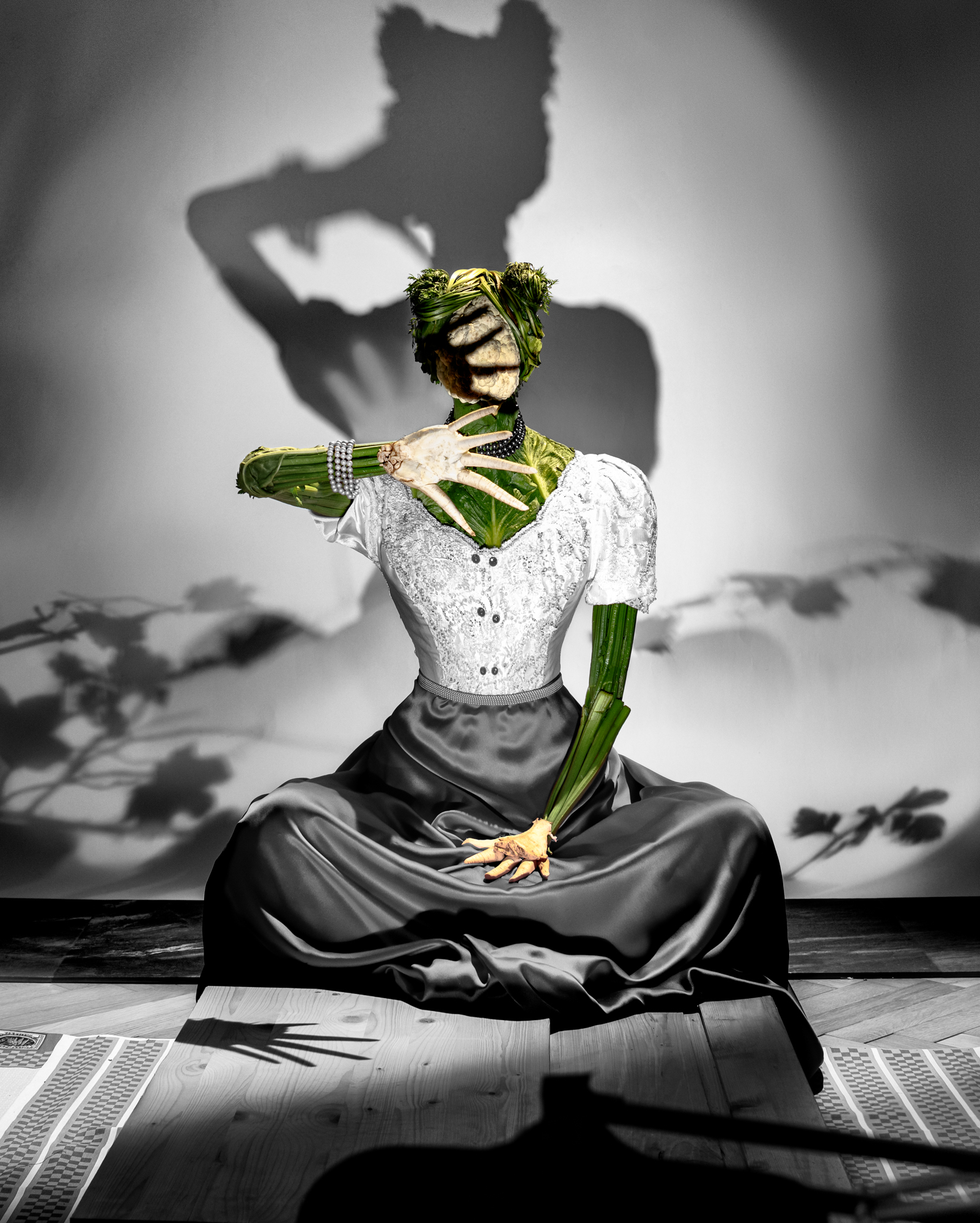Fashion meets Food. A figure made out of cabbage, cauliflower and celery root resembling a woman sitting cross legged with her right hand covering her head from the harsh light falling on her. Her shadow falling on the wall behind her.