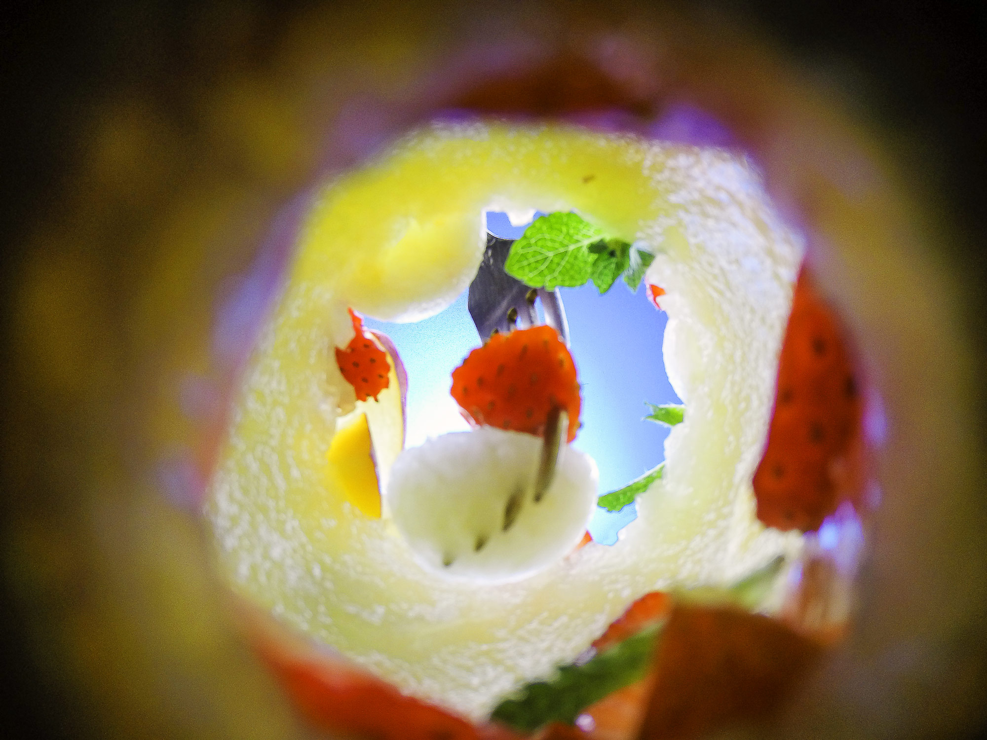 Inside food photo series, depicting a close up view from the bottom of a fruit salad served in a carved out melon. Looking up as a fork picks out a piece of melon and strawberry.