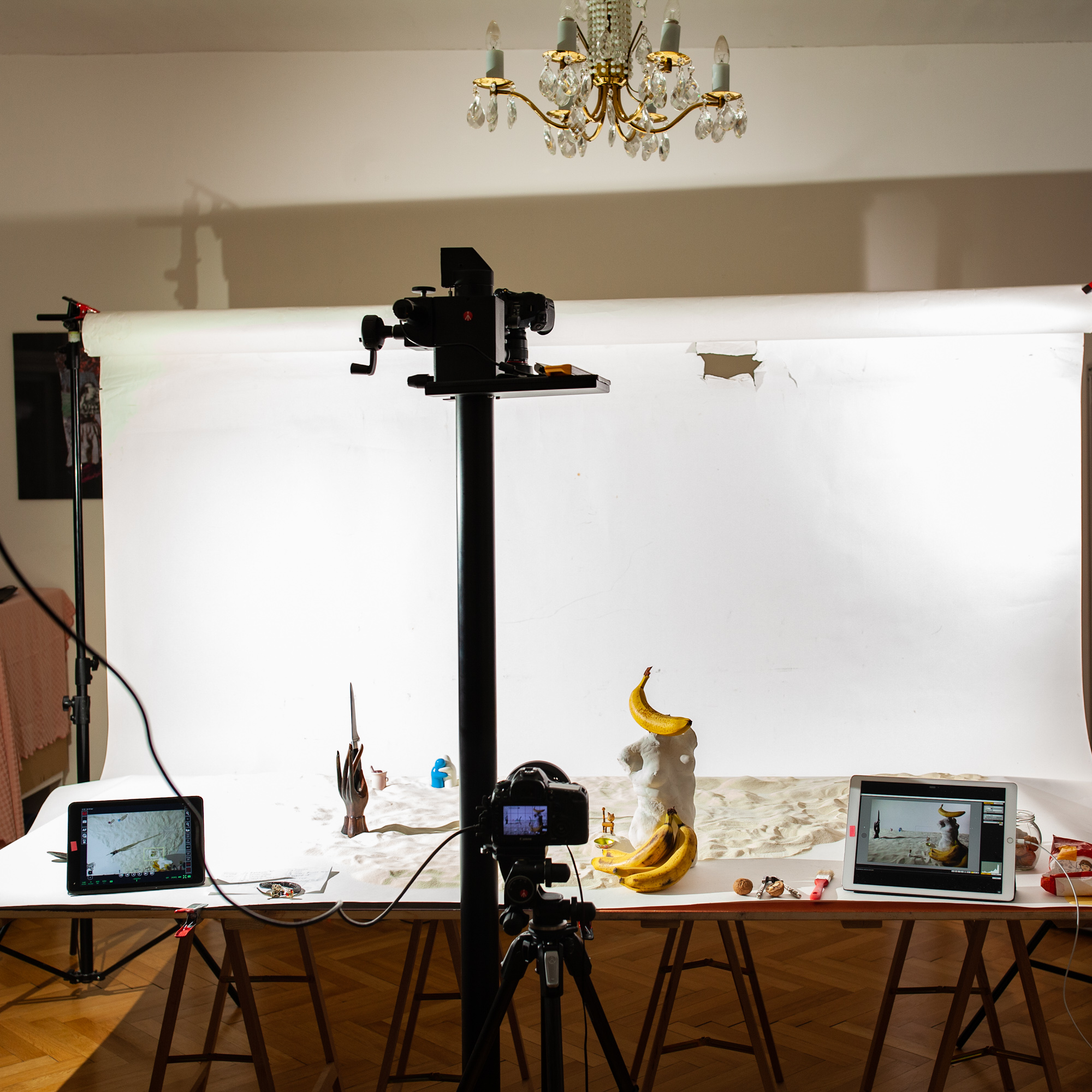 Behind the scenes of foodlydoodlydoo's vegan banana bread recipe. The photo shows the preparation of a scene. A statue of a naked women's torso decorated with bananas is seen as well as a wooden hand holding a knife. Cameras and lights are set around the scene.