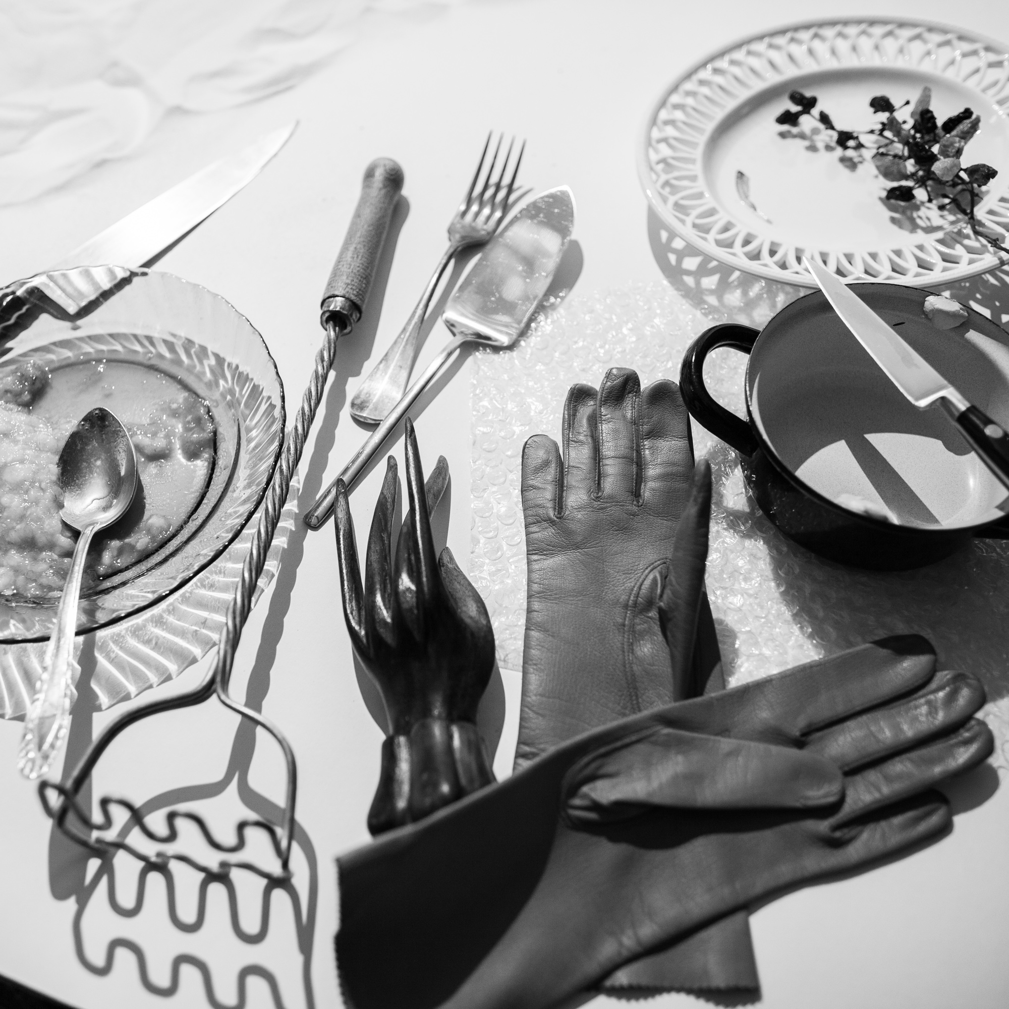 Behind the scenes of foodlydoodlydoo's vegan banana bread recipe. The photo shows the different utensils and props used fo the scene. Such as a pair of gloves, knifes, a wooden hand and some plates.