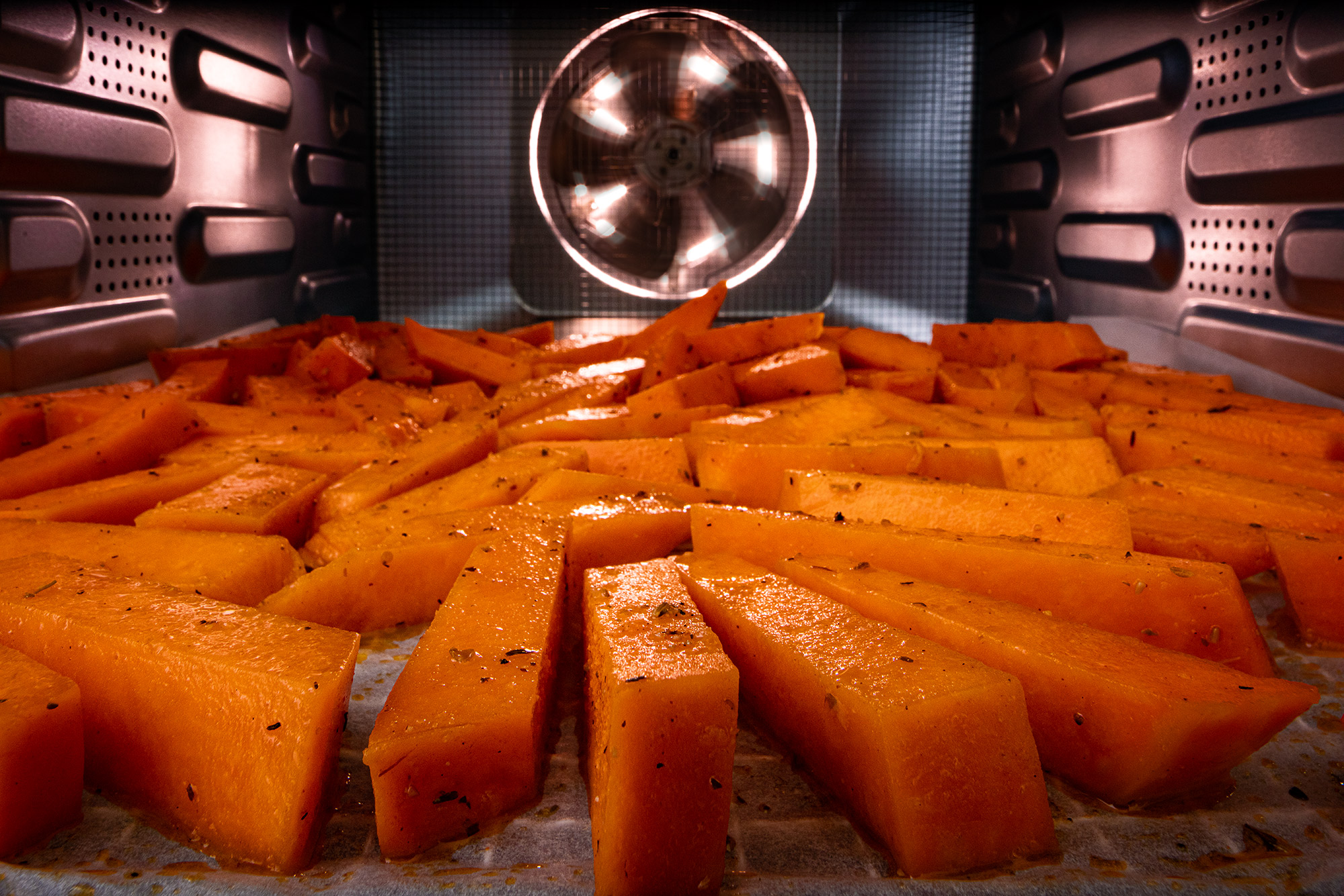 Second step for making baked pumpkin fries.In chunks cut pumpkin pieces laid out on backing paper in an oven.
