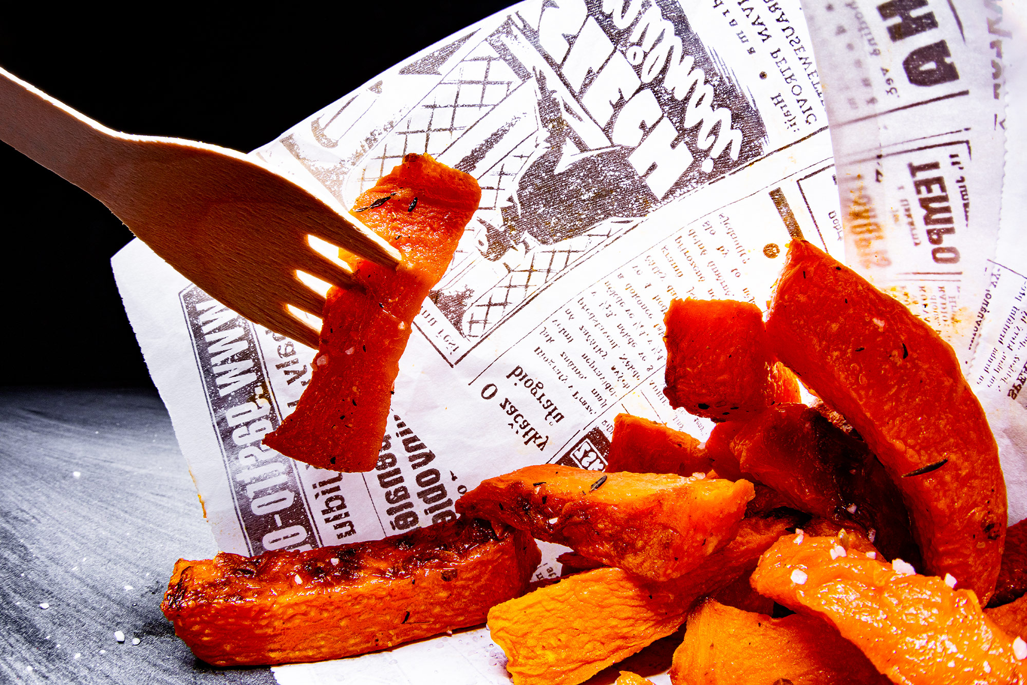 A portion of backed pumpkin fries wrapped in a newspaper. A single frie is picked up on a wooden fork.